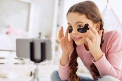 Blogger pre-adolescente optimista de la belleza que aplica remiendos del debajo-ojo Foto de archivo