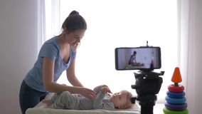 Blogger profession, modern mother vlogger changes clothes of kid boy while recording training video on mobile phone for. Followers in social networks in stock footage