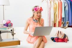 Blogger que se sienta en el sofá y que usa el ordenador fotos de archivo