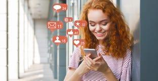 Blogger que usa el tel?fono con los iconos sociales de la notificaci?n de los medios imagenes de archivo