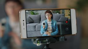 Blogger recording video about digital watch using smartphone camera at home. Focus on smart phone screen. Blogging, devices and social media content concept stock footage