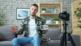 Blogger recording video about virtual reality glasses talking holding gadget. Cheerful blogger young man is recording video about virtual reality glasses talking stock footage