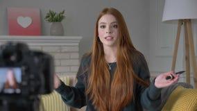 Blogger ruivo novo da menina, sorrindo, falando na câmera, mostrando uma compra nova, cosméticos, fundação, ocultador filme