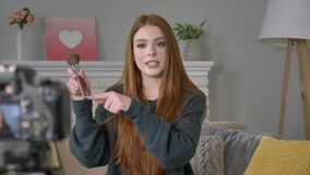 Blogger ruivo novo da menina, sorrindo, falando na câmera, mostrando uma compra nova, escova da composição, conceito da composiçã vídeos de arquivo