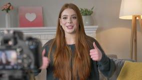Blogger ruivo novo da menina, sorrindo, feliz, falando na câmera, mostrando os gestos, pedindo para subscrever ao video estoque