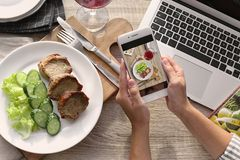 Blogger taking photo of food with mobile phone. Closeup royalty free stock image