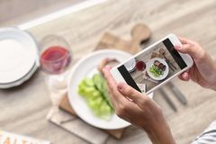 Blogger taking photo of food with mobile phone. Closeup. Space for text royalty free stock photo