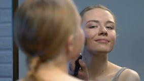 Blogger teenager di bellezza che applica la polvere della pelle e che si gira verso la macchina fotografica, segreti di bellezza archivi video