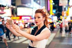 Blogger turístico hermoso de la moda de la mujer que toma el selfie de la foto en cuadrado de la noche en New York City Imagen de archivo