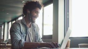 Blogger unter Verwendung des Laptops auf Tabelle im Café stock video