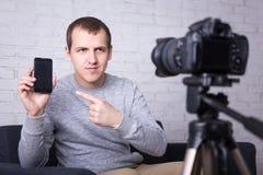 Blogger video que hace el nuevo vídeo sobre los teléfonos elegantes Imagen de archivo libre de regalías