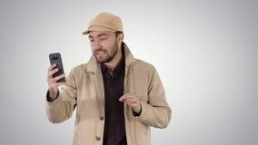 Blogger w okopie z magnetofonowym wideo na jego telefonie podczas gdy chodzący na gradientowym tle zbiory wideo