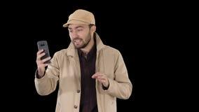 Blogger w okopie z magnetofonowym wideo na jego telefonie podczas gdy chodz?cy, Alfa kana? zdjęcie wideo