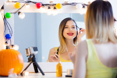 Blogger woman applying cosmetics at camera Royalty Free Stock Photos