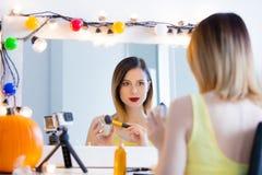 Blogger woman applying cosmetics at camera Royalty Free Stock Images