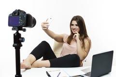 Bloggerconcepten Vrolijke Kaukasische Vrouwelijke Vlogger die Selfie op Cellphone voor Blog maken geïsoleerd tegen wit Het stelle royalty-vrije stock fotografie