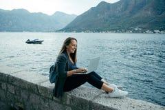 Bloggerkvinnan i grå kofta och blåttryggsäck skriver på en varv Royaltyfri Foto