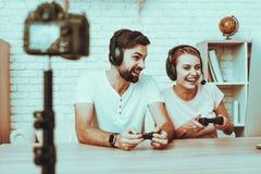 Bloggers, die ein Videospiel auf Konsole spielen lizenzfreie stockfotos