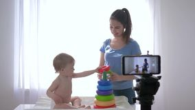 Bloggers family, lovely toddler boy with women blogger played by educational toys and relieves himself in streaming live. On camera on smartphone for stock video footage
