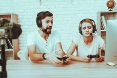 Bloggers que juegan a un videojuego en la consola imagenes de archivo
