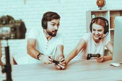 Bloggers que juegan a un videojuego en la consola foto de archivo