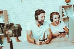 Bloggers que juegan a un videojuego en la consola foto de archivo libre de regalías