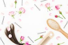 Bloggersamenstelling met kam voor haar het stileren, haarspeldje en roze bloemen op witte achtergrond Vlak leg, hoogste mening stock afbeelding