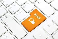 Bloggeschäftskonzept, -text und -ikone. Orange Knopf oder Schlüssel auf weißer Tastatur Lizenzfreies Stockbild