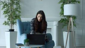 blogging的端庄的妇女工作在膝上型计算机个人计算机和 股票录像
