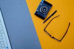 Blogging, blog and blogger or social media concept: computer keyboard and glasses, retro photo camera on a yellow background. Flat. Lay royalty free stock images