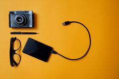 Blogging, blog and blogger or social media concept: glasses, photo camera and an external hard drive on a yellow background. Flat. Lay royalty free stock photo