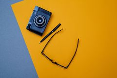 Blogging, blog and blogger or social media concept: glasses, photo camera and a pen on the yellow background. Flat lay.  stock image