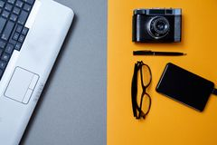 Blogging, blog and blogger or social media concept: laptop and glasses, photo camera and an external hard drive on a yellow. Background. Flat lay stock photography