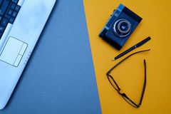 Blogging, blog and blogger or social media concept: laptop and glasses, retro photo camera on a yellow background. Flat lay.  stock photo