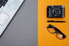 Blogging, blog and blogger or social media concept: laptop and glasses, retro photo camera on a yellow background. Flat lay.  stock photography