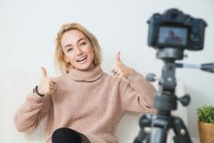 Blogging concept. Young female vlogger next to video camera at home. Beautiful woman recording vlog message at home for her internet channel Royalty Free Stock Images
