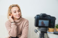 Young female vlogger next to camera at home. recording video for blog. Blogging concept. Young female vlogger next to video camera at home. Beautiful woman Royalty Free Stock Photo