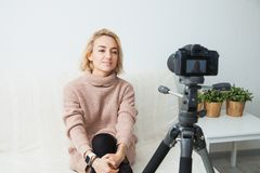 Young female vlogger next to camera at home. recording video for blog. Blogging concept. Young female vlogger next to video camera at home. Beautiful woman Stock Image