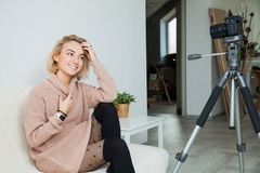 Blogging concept. Young female vlogger next to video camera at home. Beautiful woman recording vlog message at home for her internet channel royalty free stock photos