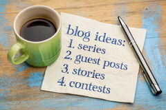 Blogging ideas list. Series, guest post, stories, contests - handwriting on a napkin with a cup of espresso coffee stock images