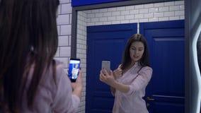 Blogging, jonge vrouw registreert video op mobiele telefoon die zich voor spiegel in toilet bevinden stock video