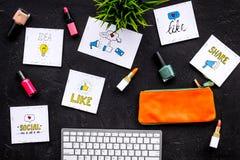 Blogging Konzept der Schönheit Bearbeiten Sie Schreibtisch mit Tastatur, Kosmetik und Social Media-Ikonen auf schwarzer Tischplat Stockfotos