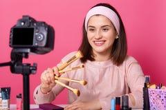Blogging modernt teknologi och folkbegrepp Den lyckliga le videopd bloggeren för kvinnaskönhet rymmer borstar för makeup, medan a fotografering för bildbyråer