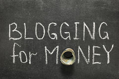 Blogging for money. Phrase handwritten on blackboard with money roll instead of O stock images