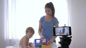 Blogging, nice child boy with girl played by educational toys and recording live tutorial video on mobile phone for. Followers in social networks in bright room stock footage