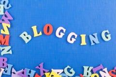 BLOGGING ord på blå bakgrund som komponeras från träbokstäver för färgrikt abc-alfabetkvarter, kopieringsutrymme för annonstext Arkivfoton