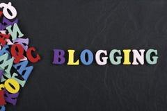 BLOGGING ord på svart brädebakgrund som komponeras från träbokstäver för färgrikt abc-alfabetkvarter, kopieringsutrymme för annon Royaltyfri Fotografi
