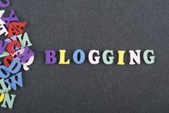 BLOGGING ord på svart brädebakgrund som komponeras från träbokstäver för färgrikt abc-alfabetkvarter, kopieringsutrymme för annon Arkivbilder