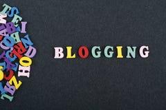 BLOGGING ord på svart brädebakgrund som komponeras från träbokstäver för färgrikt abc-alfabetkvarter, kopieringsutrymme för annon Royaltyfri Bild