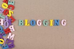 BLOGGING ord på träbakgrund som komponeras från träbokstäver för färgrikt abc-alfabetkvarter, kopieringsutrymme för annonstext Fotografering för Bildbyråer